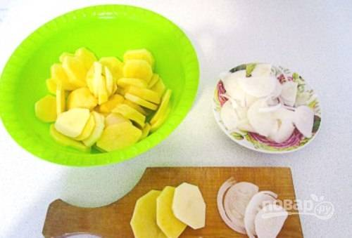 Картофель нарежьте кружками, а лук —  полукольцами, предварительно почистив овощи.