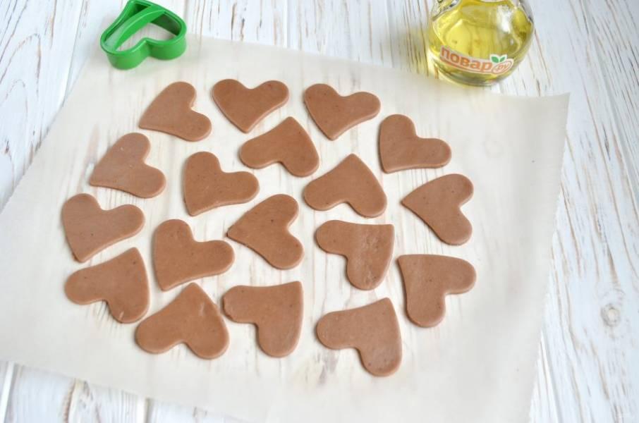 Уберите лишнее тесто. Осторожно перенесите пергамент с печеньем на противень и отправьте в духовку на 10 минут.
