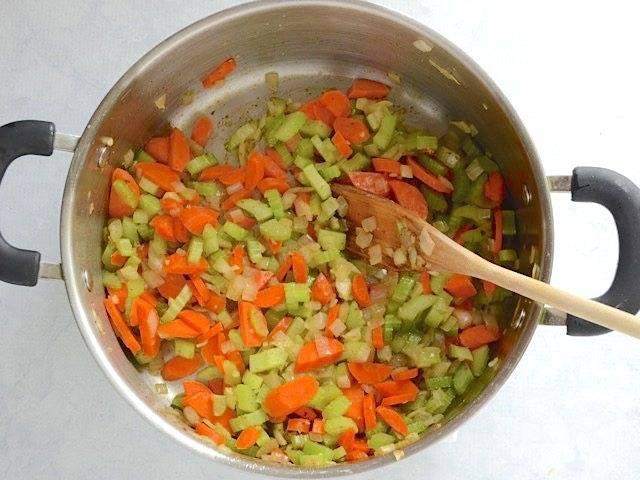 3.Нарежьте небольшими кусочками лук, тонкими полукольцами морковь и сельдерей, измельчите чеснок. Выложите сперва лук в кастрюлю с жиром, обжаривайте несколько минут, затем добавьте морковь и сельдерей, в самом конце выложите чеснок, готовьте еще 1 минуту.