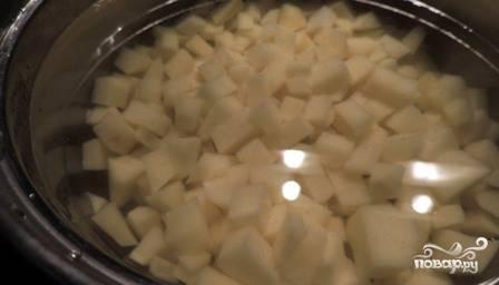 Наливаем в кастрюлю примерно 2 л воды, ставим на огонь. Картофель нарезаем небольшими кубиками и отправляем в кастрюлю, пусть варится.