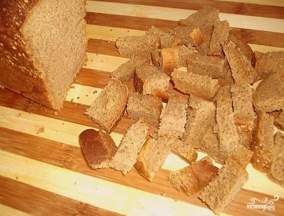Хлеб натереть чесноком, нарезать на небольшие кубики, сбрызнуть растительным маслом (буквально 1 столовая ложка) и поджарить в духовке.