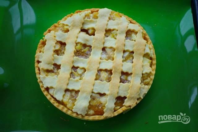 Тесто раскатайте в тонкий пласт, разрежьте на тонкие полоски, разместите их поверх яблочной начинки в виде решетки. Поставьте пирог запекаться в духовку при 220 °С на 15 минут. Снимите кольцо, дайте пирогу остыть.