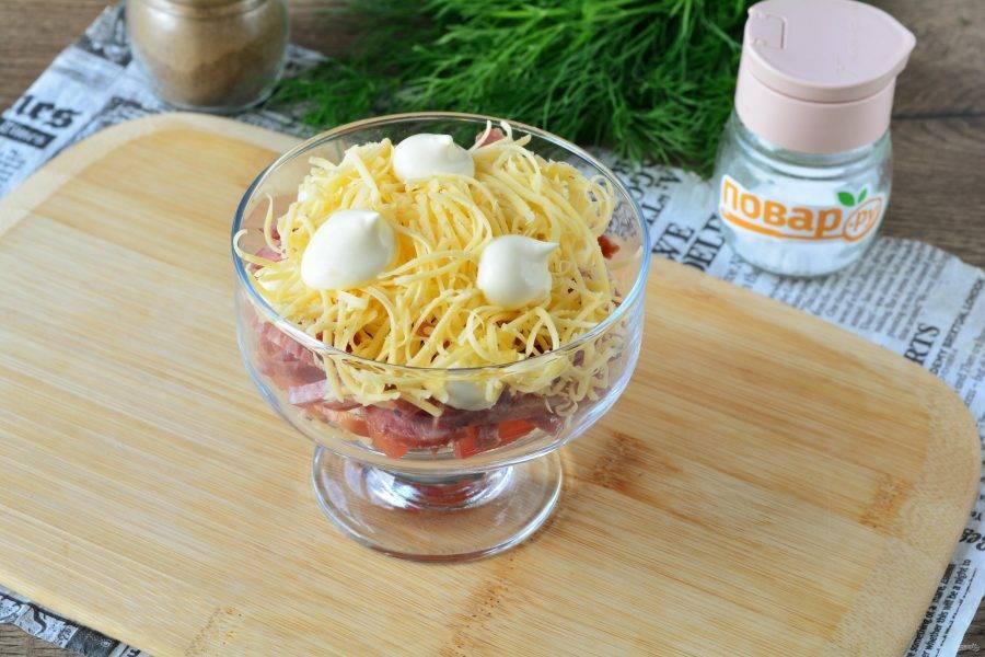 Присыпьте салат тертым сыром и полейте майонезом.