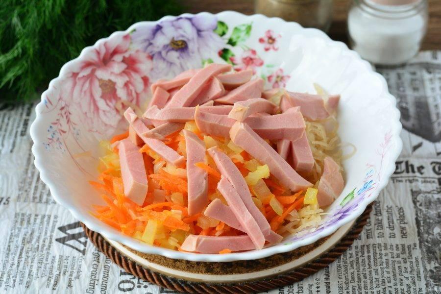 Всыпьте колбасу в салат, перемешайте. Добавьте чуть соли и перца. Если масла мало, влейте еще немного.
