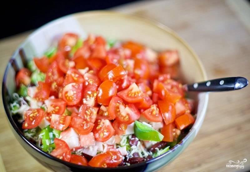 Последними в салат с крабовыми палочками и фасолью идут помидоры. Нарежьте их мелко.