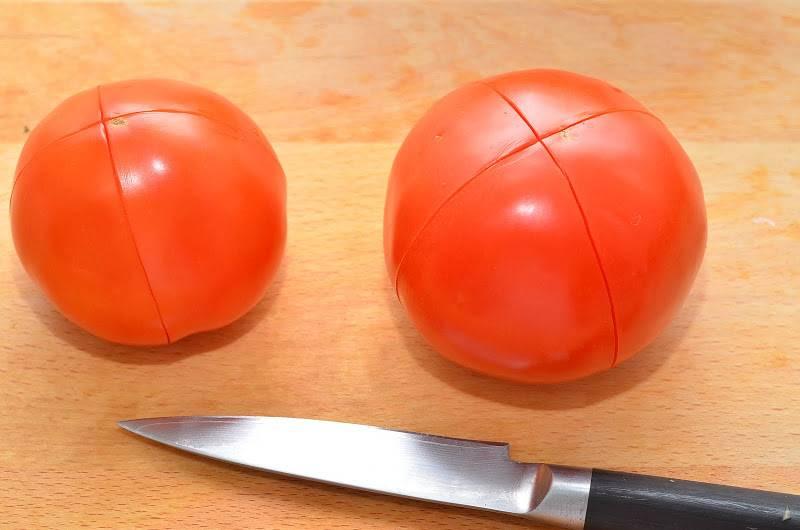 На помидорах делаем крестообразные надрезы и заливаем их полностью кипятком, оставляем так на 3 минуты.