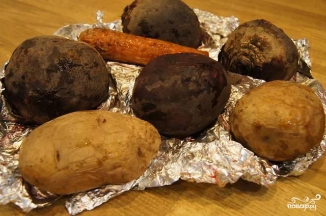 Овощи мы будем запекать вместе, поэтому желательно подобрать их так, чтобы свекла была среднего размера, а морковь и картошка крупные. Таким образом, они смогут равномерно пропечься  духовке. Итак, промываем овощи под холодной водой и хорошенько вытираем их. Кладем в середину фольги и заворачиваем, кладем в духовку. Температура приготовления 175 градусов, время 1 час. Когда овощи будут готовы, необходимо дождаться, пока они немного остынут.