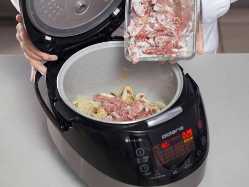 """Измельчите лук. Влейте в чашу мультиварки оливковое масло, обжарьте лук в режиме """"Жарка"""" до прозрачности. Добавьте порезанные ломтиками грибы, жарьте еще 10 минут. Затем добавьте мясо и готовьте еще 10 минут."""