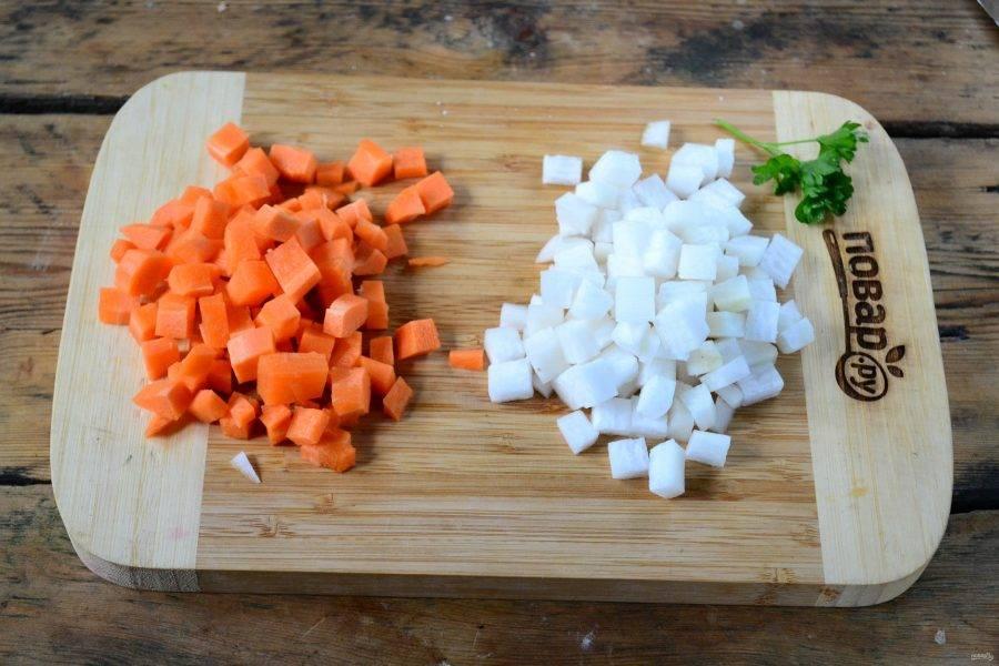 Вскипятите примерно 2 литра воды, добавив в нее лавровый лист. Морковь и корень сельдерея порежьте мелким кубиком. Отправьте их в кипящую воду.