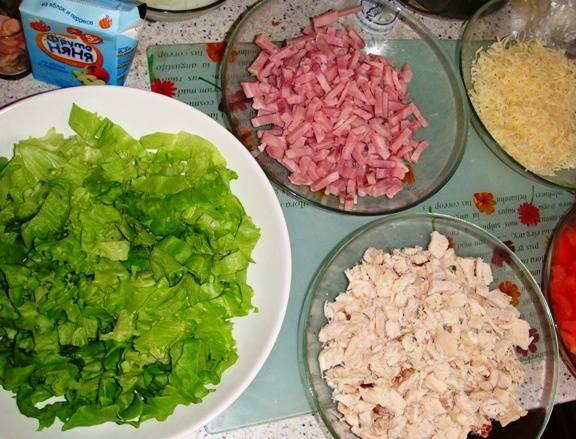 Мелко нарежьте ветчину, отваренную курятину и помидоры. Зеленый салат порвите руками, а сыр натрите.