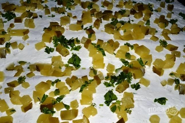 Затем разворачиваем один лист лаваша и равномерно размазываем по нему творожный крем, дальше посыпаем порезанными огурцами и зеленью.
