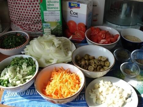 Подготовим остальные продукты: лук нарезаем полукольцами, морковку трем на терке, оливки режем пополам, чеснок — на пластинки. Помидоры режем небольшими кусочками, сельдерей — небольшими кубиками.