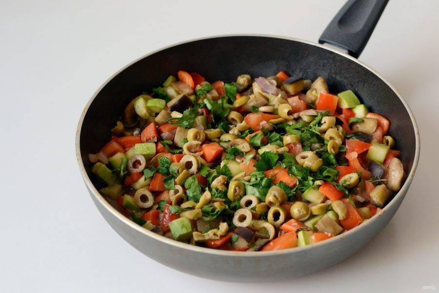 Посолите, поперчите и добавьте молотый перец чили. Влейте в сковороду воду. Добавьте мелко порубленную петрушку, оливки и чабрец. Тушите овощи 10 минут до готовности.