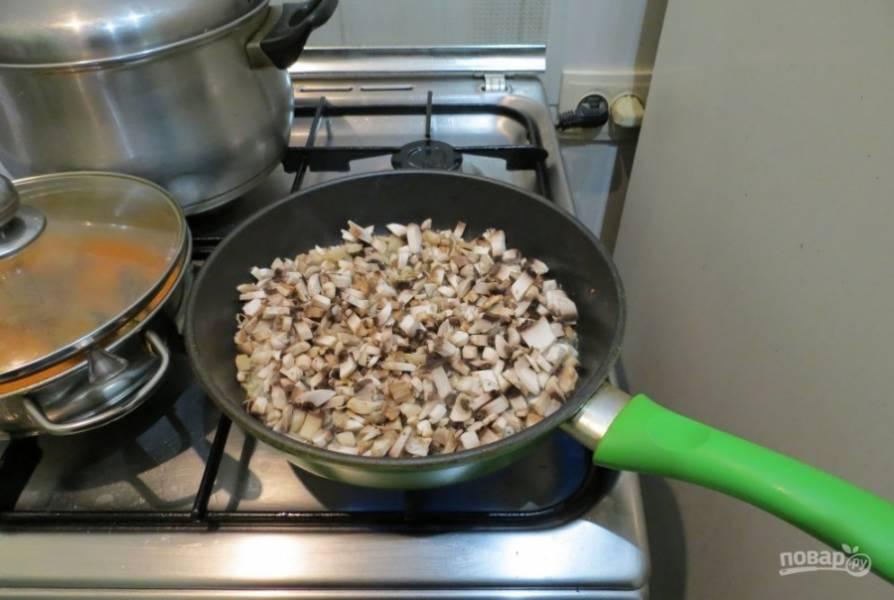 Как лук станет прозрачным, добавьте к нему промытые и нарезанные шампиньоны. Посолите их и жарьте пару минут.