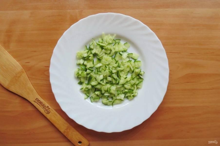 Свежий огурец нарежьте мелким кубиком и выложите первым слоем салата.