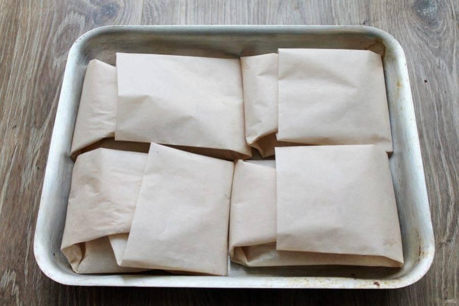 Выложите конвертики из пергамента на противень в один слой.