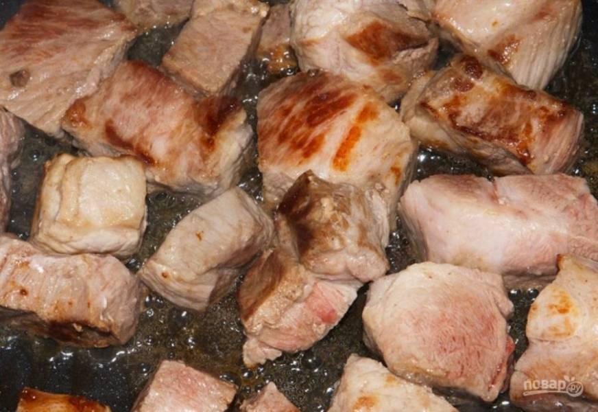 Промойте свинину под холодной водой и высушите его бумажным полотенцем. Порежьте мясо на кубики, обжарьте их с растительным маслом на среднем огне в течение 10 минут до золотистой корочки.
