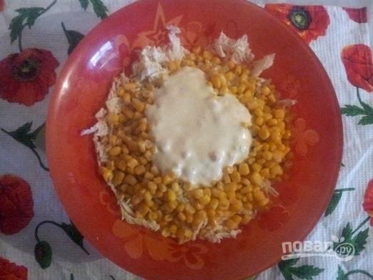 К майонезу или сметане добавляем выдавленный через пресс чеснок и перемешиваем. Затем добавляем приготовленный соус к капусте и кукурузе.