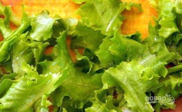 Листья салата хорошенько промойте под холодной проточной водой. Выложите их на полотенце, чтобы обсушить. Порвите листья салата руками на крупные куски.
