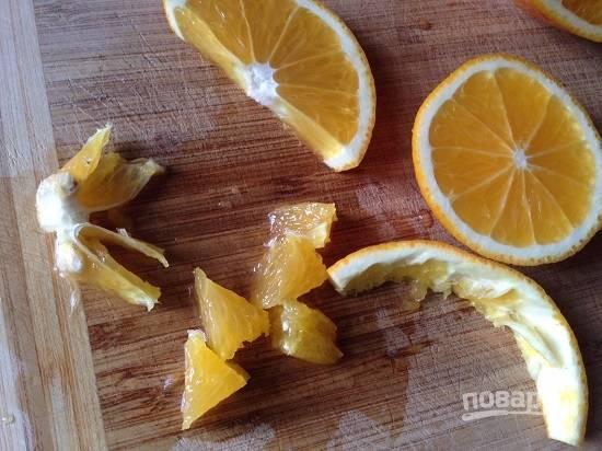 Половину апельсина оставим, а остальное нарежем полукружками и филируем, нарезаем ломтики без перепонок.