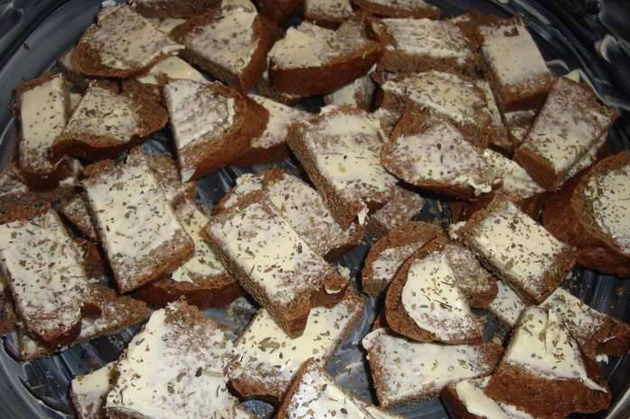Хлеб нарежьте ломтиками, намажьте сливочным маслом, затем порежьте кубиками. Кладем хлеб в смазанную маслом форму для запекания, присыпаем прованскими травами.