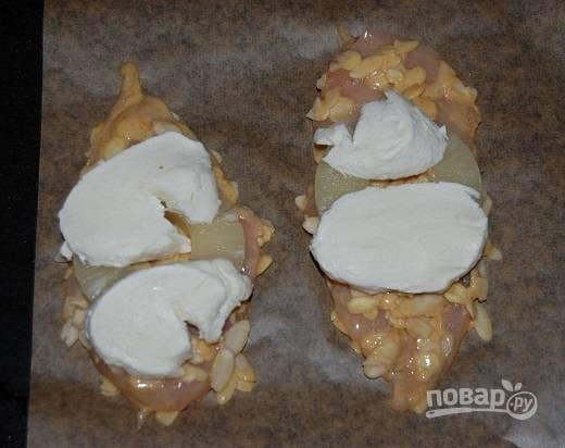 Обмакиваем отбивную в тесто, затем обваливаем в миндальных лепестках. Выкладываем на противень, застеленный пергаментом. На каждую отбивную выложим кружок ананаса и покрываем его моцареллой.