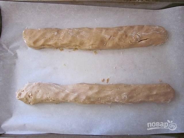 4.Разделите тесто на 2 части и каждую раскатайте в колбаску, выложите на противень с пергаментом.