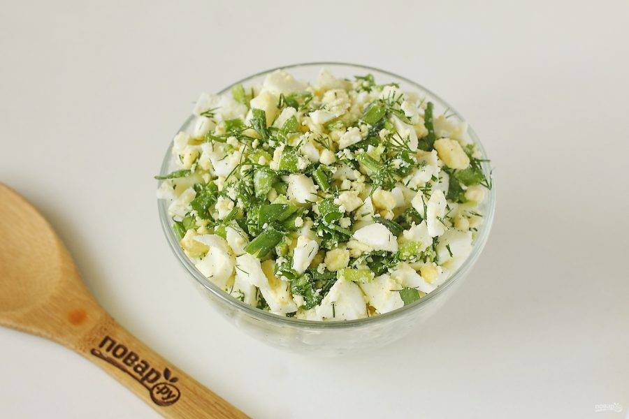 Для начинки соедините нарезанные кубиками вареные яйца и рубленую зелень. Соль и перец добавьте по вкусу.
