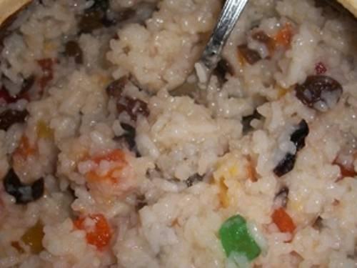 За 3 минуты до готовности (рис уже должен быть мягким) добавьте цукаты и изюм. Влейте жидкий мед или растворенный сахар и хорошо перемешайте ложкой. Выключайте. Дайте остыть — блюдо едят холодным.