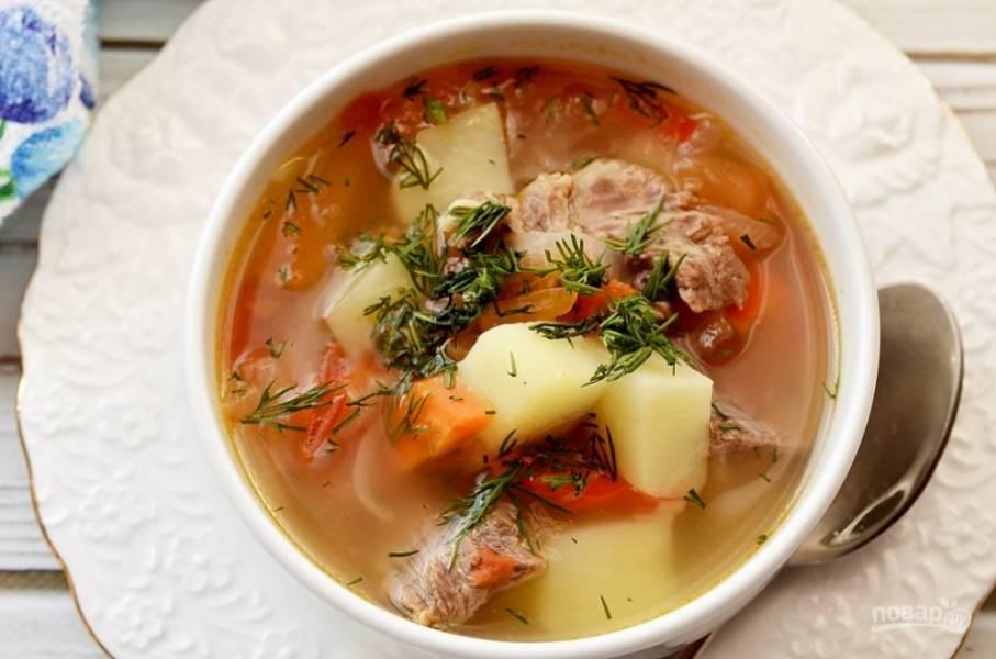 В тарелки выложите мясо, овощи, долейте бульон, посыпьте рубленой зеленью и молотым перцем.