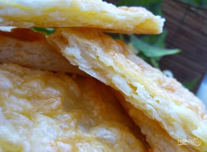 Раскатайте стопку лепёшек в 7 мм. толщиной. Разделите их на квадратики и смажьте белком. Присыпьте сыром и солью каждый.
