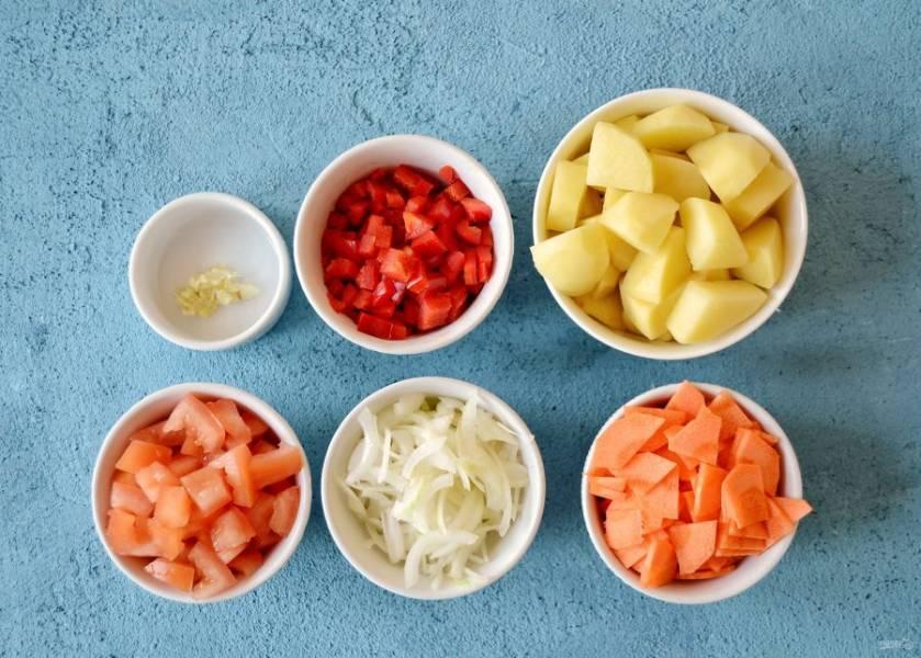 Картошку очистите и нарежьте на крупные ломтики. Лук нарежьте на тонкие перья, раздавите зубчик чеснока. Помидор, морковь и болгарский перец нарежьте на ломтики среднего размера.