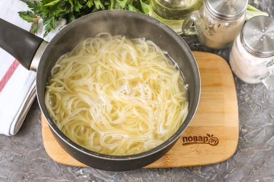 Влейте в казан или ковш воду, посолите ее и доведите до кипения. Выложите в воду спагетти и отварите их согласно инструкции на упаковке.