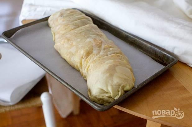 9. С помощью полотенца (салфетки, пергамента) аккуратно сверните рулет. Залепите края и выложите штрудель на противень, застеленный пергаментом. Смажьте маслом и отправьте в духовку.