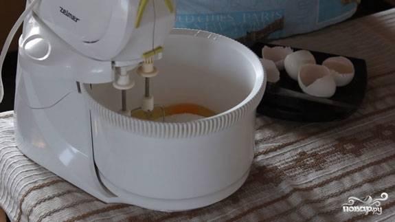 2. В глубокую мисочку отправьте яйца со щепоткой соли. Всыпьте сахар и начните взбивать. Очень удобно использовать для этого технику, но можно и венчиком. Масса должна стать пышной и однородной.