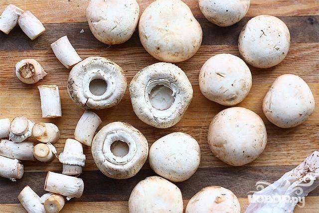 2. Разогреть духовку до 175 градусов. Тщательно очистить грибы и обрезать ножки. Поместить грибные шляпки на небольшой противень. Отложить в сторону.