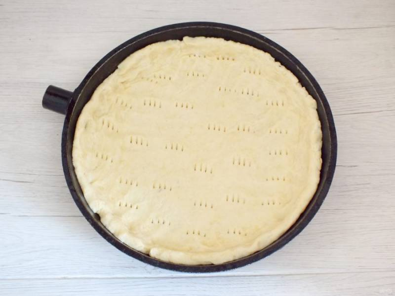 Возьмите форму с бортиками, смажьте тонким слоем растительного масла. Выложите тесто, сделайте бортики. Вилкой сделайте проколы по всей поверхности теста.