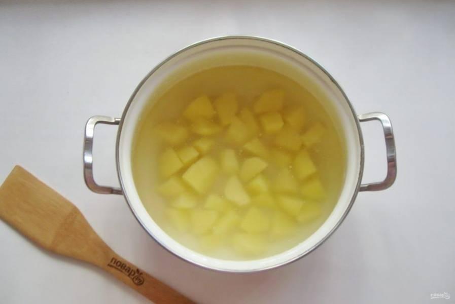В кастрюлю налейте куриный бульон и выложите картофель, нарезанный кубиками.