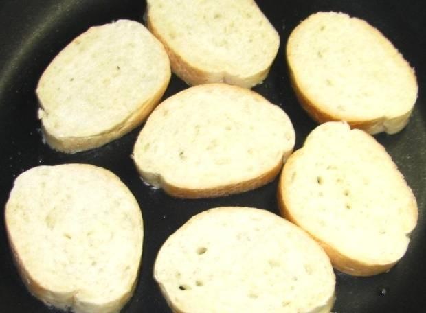 В сковороде разогреваем растительное масло (совсем немного) и обжариваем на нем ломтики багета до румяной корочки, но только с одной стороны.