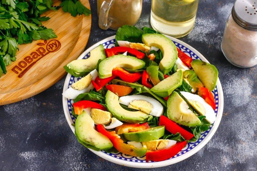 Последним очистите от кожуры авокадо. Удалите косточку и нарежьте мякоть ломтиками, выкладывая их между остальными ингредиентами на тарелке.