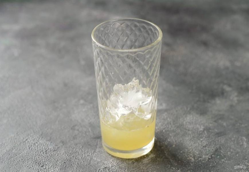 На дно стакана выложите лед. Заполните одну треть стакана соком лайма с лимоном.