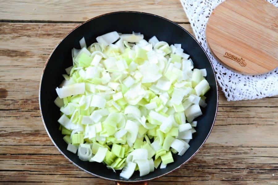 Лук репчатый и лук-порей нарежьте некрупным кубиком и отправьте в сковороду с разогретым растительным маслом. Обжарьте на среднем огне в течение 7-10 минут.