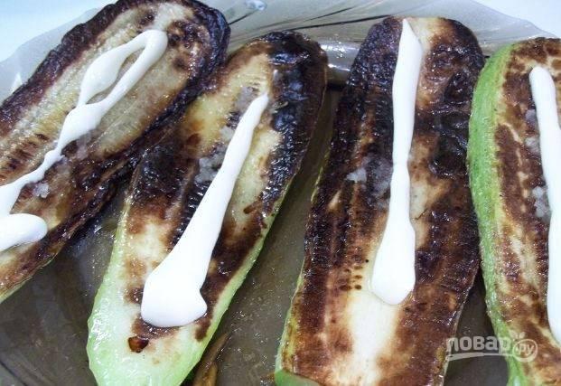 Обжаренные кабачки немного остудите и выложите на тарелку. Затем пропустите через пресс очищенный чеснок, смажьте им кабачки. Поверх чеснока выложите на овощи немного майонеза.