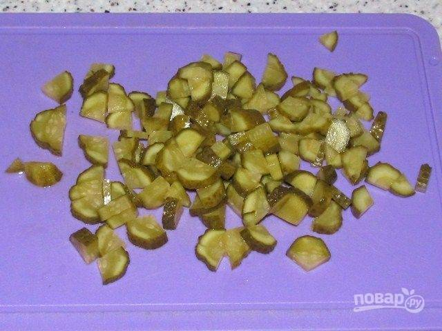 5. Нарезаем соленые огурцы кубиками и тоже отправляем их к остальным ингредиентам.
