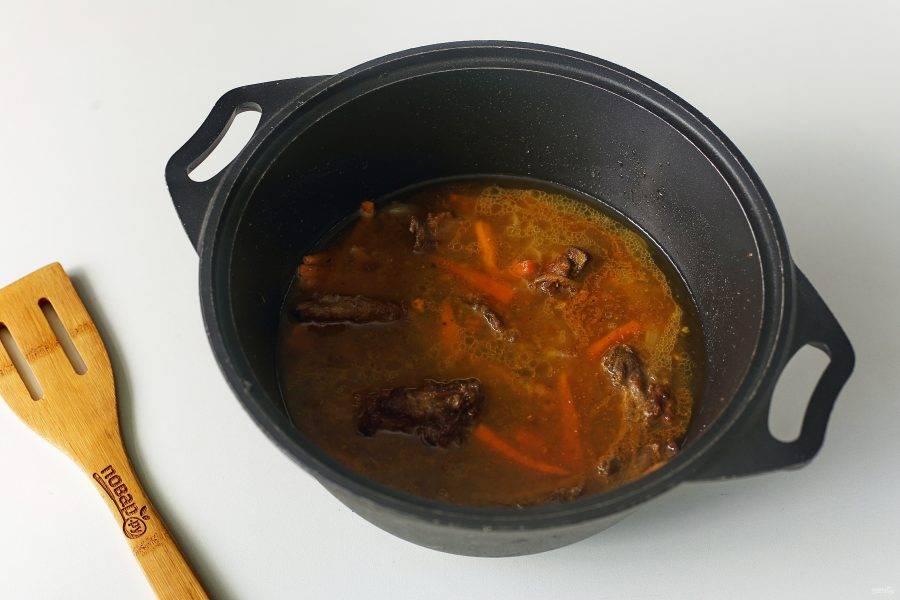 Затем добавьте воду, чтобы она лишь слегка покрывала мясо, соль по вкусу, специи и тушите на небольшом огне около 20 минут.