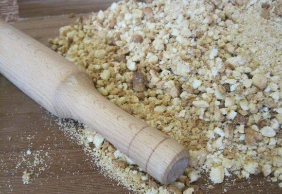 Арахис и готовое остывшее тесто растолочь скалкой.