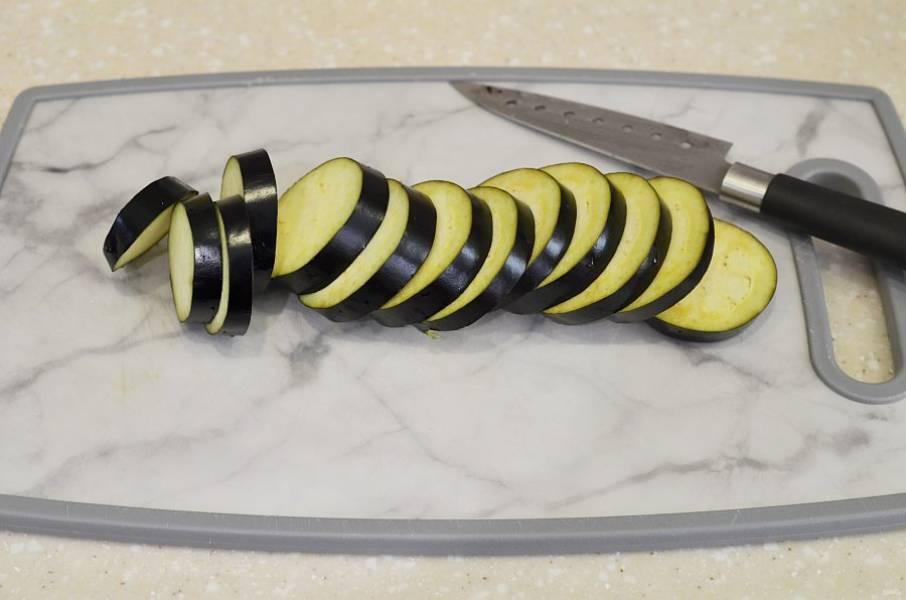 2. Баклажаны нарежьте кружками толщиной 1 см. Положите на 15 минут в соленую воду, затем воду слейте.