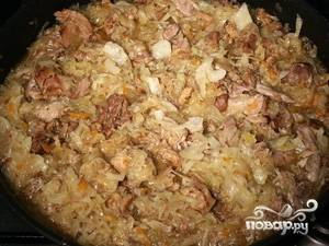 В высокой сковороде смешиваем мясо, лук, добавляем туда капусту и тушим около получаса на медленном огне.