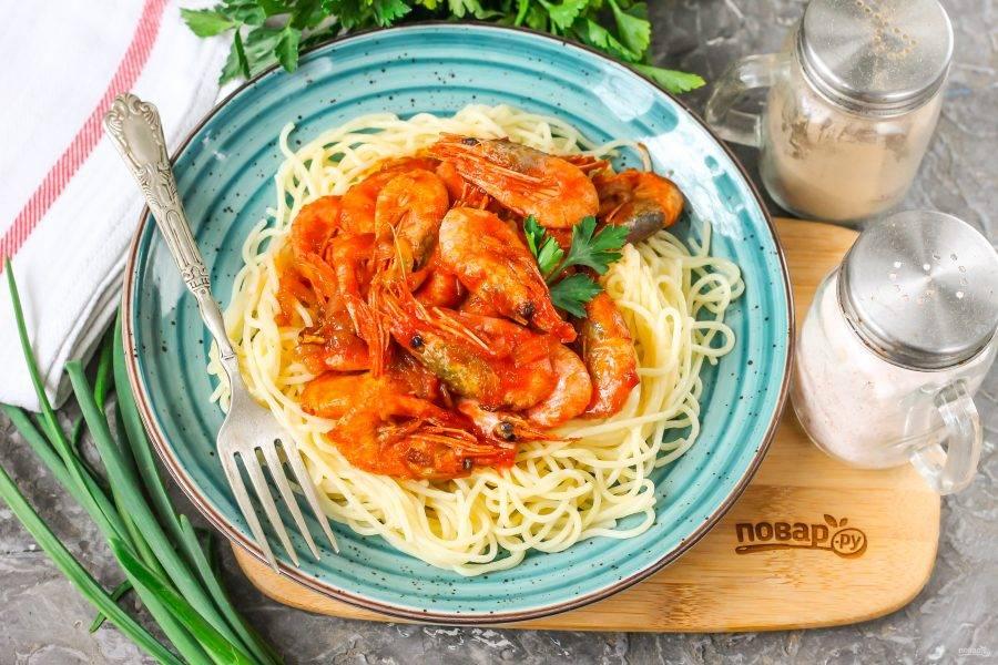 Со спагетти слейте воду, выложите их на тарелку. Сверху выложите креветки в томатном соусе, и подайте блюдо к столу горячим. По желанию спагетти можно добавить в сковороду и перемешать все вместе.