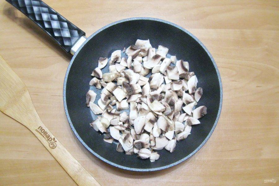 Приготовьте начинку для кулебяки. Шампиньоны очистите и нарежьте. Выложите в сковороду. Налейте подсолнечное масло и поджарьте грибы до испарения влаги.